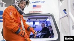 Astronaut Randy Bresnik prepares to enter Boeing CST-100 spacecraft for a fit check evaluation at the company's Houston Product Support Center. On Tuesday, Sept. 16, 2014 (NASA)