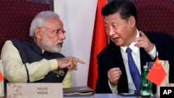 FILE - Indian Prime Minister Narendra Modi, left, talks with Chinese President Xi Jinping during the BRICS summit in Goa, India, Oct. 16, 2016. China and India may have ended a tense border standoff for now, but their longstanding rivalry raises questions.