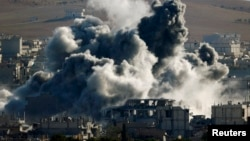 An explosion following an air strike is seen in central Kobani, Nov. 9, 2014. Picture taken from the Turkish side of the Turkish-Syrian border.