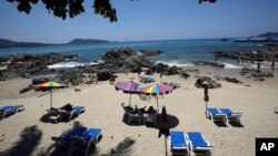 FILE - Tourists spend time on Patong Beach in Phuket province, southern Thailand. Thailand's sapphire blue waters, wildlife parks, delicious cuisine and raunchy red light districts have attracted tourists for decades, March 13, 2014.
