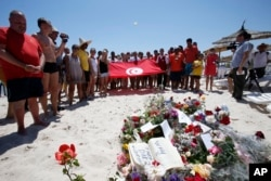 FILE - People, some displaying a Tunisian flag, stand in silence next to flowers during a gathering at the scene of the attack in Sousse, Tunisia, June 28, 2015.