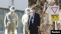日本卫生官员戴着防疫口罩在东京的国立国际医疗研究中心等候从武汉撤回国的日本侨民。(2020年1月30日)