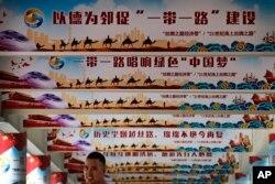 """2018年6月29日,在北京举行的一次活动中展示的中国国家主席习近平的""""中国梦""""和""""一带一路""""政策上网宣传牌,一名男子站在下面。"""