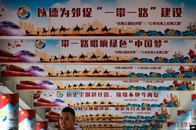 """2018年6月29日,在北京舉行的一次活動中展示的中國國家主席習近平的""""中國夢""""和""""一帶一路""""政策上網宣傳牌,一名男子站在下面。"""