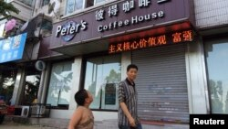 A boy looks up as he walks past the closed coffee shop owned by Canadian couple Kevin and Julia Dawn Garratt in Dandong, Liaoning province, August 5, 2014.