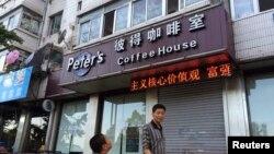 行人路过凯文·高夫妇在丹东经营的咖啡馆(2014年8月5日)