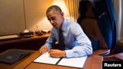 Tổng thống Obama ký 2 lệnh hành pháp về di trú trên Air Force One khi đến Las Vegas, 21/11/2014.