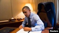 Presiden Obama menandatangani dua perintah eksekutif terkait imigrasi di ruang kerjanya dalam pesawat kepresidenan Air Force One (21/11).