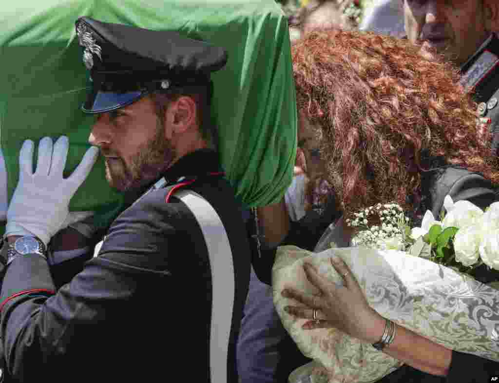 Carabinieri officer Mario Cerciello Rega's wife, Rosa Maria, right, follows the coffin of her husband during his funeral in Somma Vesuviana, near Naples, southern Italy. Two American teenagers were jailed in Rome as authorities investigate their alleged roles in the fatal stabbing of Mario on a street near their hotel.
