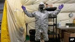 یکی از ماموران عملیات نابودسازی سلاح های شیمیایی سوریه با لباس ایمنی