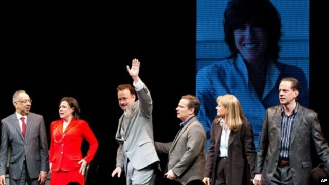 "George C. Wolfe , Maura Tierney, and Tom Hanks, with an image of Nora Ephron behind them on a large screen, at the ""Lucky Guy"" opening night, April, 1, 2013 in New York, NY."