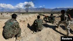 FILE - Afghan security forces take a position during a gunbattle with Taliban forces in Laghman province, Afghanistan, March 1, 2017.