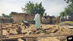 Rabiu Wada walks on the remains of his home, destroyed by flooding, in the village of Rimgim, near Dutse in northern Nigeria, 28 Sep 2010