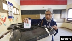 A woman casts her vote at a polling station during the second round of parliamentary elections in the Shubra area of Cairo, Egypt, Nov. 22, 2015.