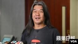 """""""长毛""""梁国雄向媒体说明获得一次性回乡证(苹果日报图片)"""