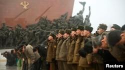 Binh sĩ Bắc Triều Tiên đứng nghiêm chào trong lúc những người khác cúi gập trước tượng đồng của cố lãnh tụ Bắc Triều Tiên Kim Il-sung và cố lãnh tụ Kim Jong Il tại Mansudae, Bình Nhưỡng, ngày 16/2/2015.