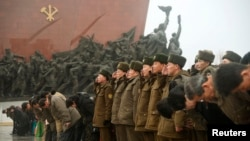 North Korean soldiers salute as others bow to bronze statues (not pictured) of North Korea's late founder Kim Il-sung and late leader Kim Jong Il at Mansudae in Pyongyang, in this photo provided by Kyodo, February 16, 2015.