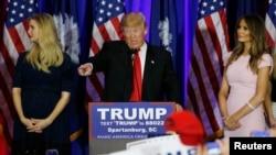 唐纳德·川普在南卡胜选集会上讲话,女儿伊万卡(左)和夫人梅拉妮娅(右)站在他身边。(2016年2月20日)