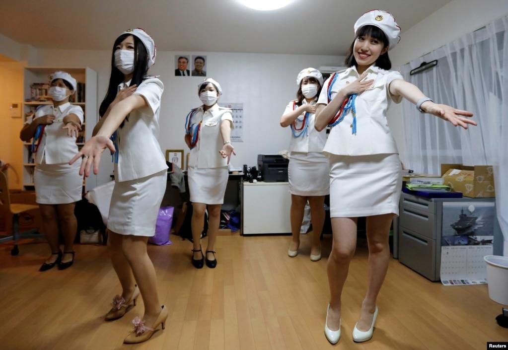 """日本的一个名叫""""先军女郎""""的朝鲜粉丝小组的成员在东京练习舞蹈(2017年10月29日)。朝鲜今年一再向日本海域发射导弹,两国关系紧张。但在日本的这个女团,穿着军装,模仿朝鲜牡丹峰乐团 的歌舞。生活中,她们也热衷朝鲜文化和艺术。日本的韩裔社区对她们褒贬不一。套用古诗来说,歌女不知专制恨,隔海犹学""""牡丹峰""""?"""