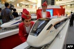 Dua peragawati menunjukkan model kereta cepat buatan China dalam pameran di Jakarta, 13 Agustus 2015. (Foto: AFP)