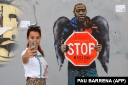 "A woman takes a selfie picture posing next to a street poster artwork by Italian urban artist Salvatore Benintende aka ""TVBOY"" depicting George Floyd with angel wings and holding a stop traffic sign against racism, in a street of Barcelona"