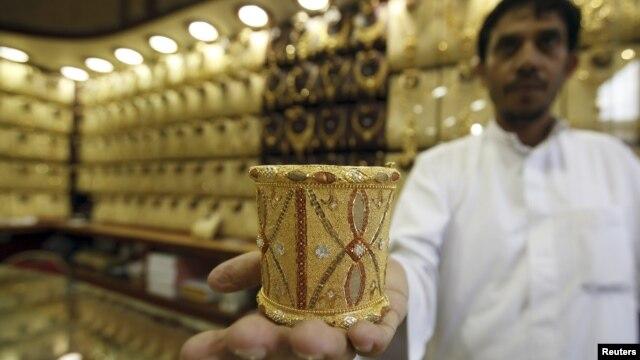 Mahdi al-Mehri dari Arab Saudi menunjukkan gelang emas yang dijual di tokonya di dekat Kabah. (Reuters/Amr Abdallah Dalsh)