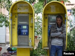 FILE - An Afghan refugee seeks shelter in a phone booth during a rainstorm in Victoria Square, where hundreds of migrants and refugees sleep, in central Athens, Greece, Sept. 21, 2015.