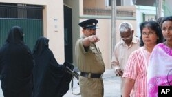 Policeman giving instruction to voters at polling station in Colombo, 26 Jan 2010