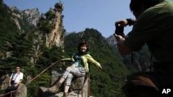 Seorang turis China tampak berpose di taman wisata Gunung Kumgang, tujuan utama wisatawan di Korea Utara (foto: dok). Pariwisata Korea Utara dari China tidak terpengaruh oleh ketegangan politik di sana.