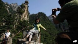 A Chinese tourist poses for a picture near a resort in North Korea's Kumgang Mountains. (2011)