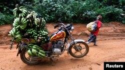 Une paysanne près d'une moto chargée de bananes, entre Mundemba et le village de Fabe, au Cameroun, le 8 juin 2012.
