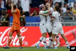 United States' Rose Lavelle, second right, celebrates with Megan Rapinoe, center, after scoring her side's second goal during the Women's World Cup final soccer match between US and The Netherlands at the Stade de Lyon in Decines