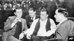 John Dillinger (center) was Public Enemy No. 1 in the 1930s. Here he is handcuffed and guarded in court as his trial date is set for March 12 at Crown Point, Ind., Feb. 9, 1934. (AP PHOTO)