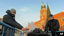 Passersby warm hands near a charcoal heater in front of the Royal Castle in Warsaw, Poland, Feb. 2, 2012.