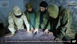FILE - Abu Mohammed al-Golani, the leader of Fatah al-Sham Front, center, is seen in this undated picture posted by the group, discussing battlefield details with field commanders over a map.