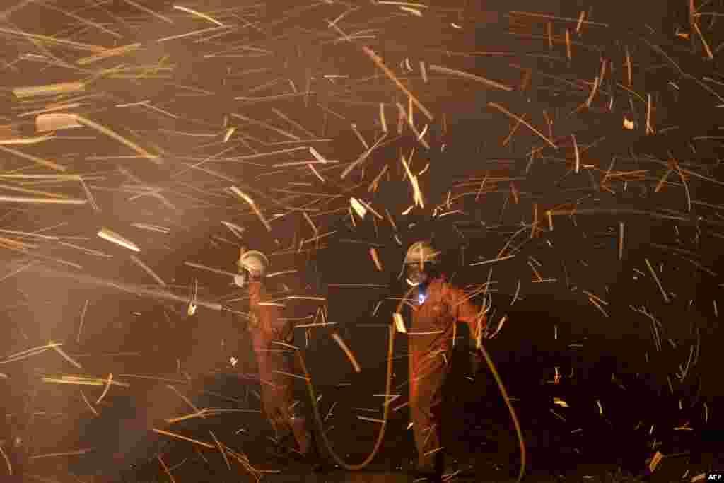 Lính cứu hỏa xịt nước ngăn chặn đám cháy rừng ở Riviera, gần La Coruna, Tây Ban Nha.