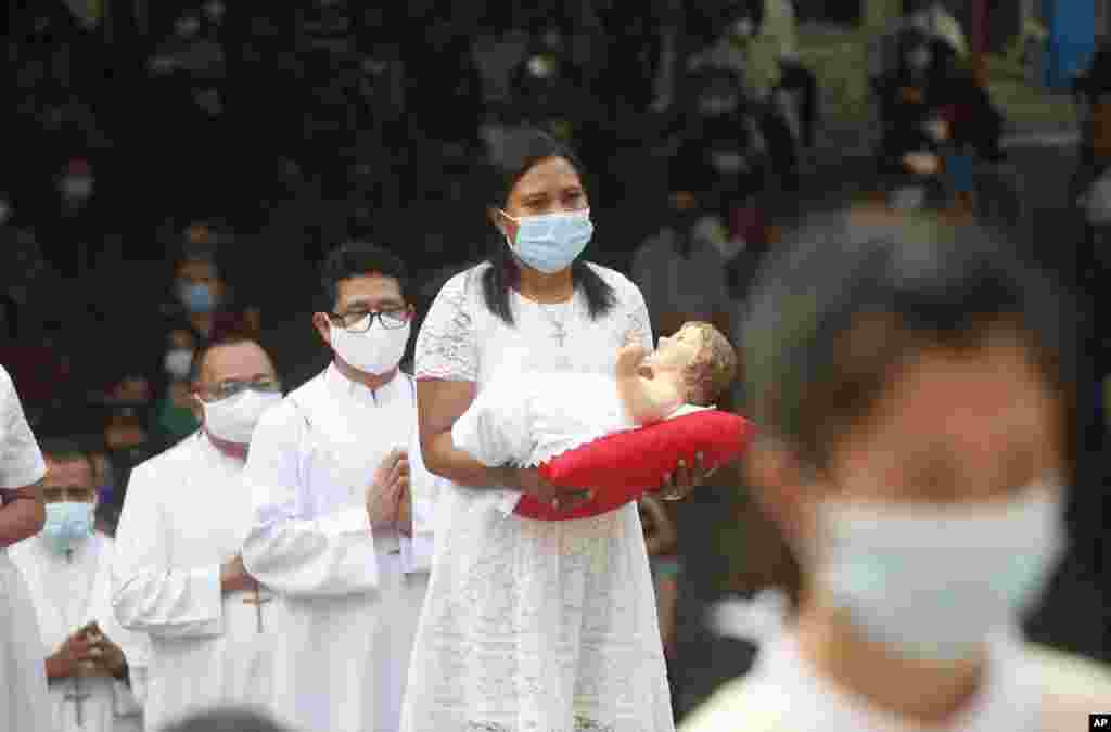 A woman, wearing face mask, carries baby Jesus statue, during a procession for a Christmas mass service at a church in Bali, Indonesia.