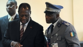 Ivory Coast's President Alassane Ouattara (L) uses an ipad prior to attending African Union talks in Addis Ababa, March 10, 2012.