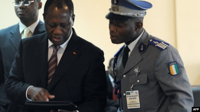Ivory Coast's internationally recognized President Alassane Ouattara (L) uses an iPad prior to attending African Union talks in Addis Ababa, March 10, 2012.