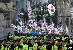 "Supporters of South Korean ousted President Park Geun-hye wave national flags and picture of Park outside of a prosecutors' office in Seoul, South Korea, March 21, 2017. Park said she was ""sorry"" to the people as she arrived Tuesday at a prosecutors' offi"