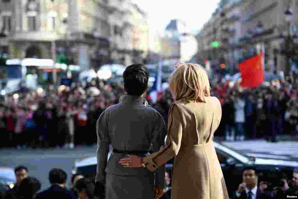 French president's wife Brigitte Macron (R) and Chinese president's wife Peng Liyuan wave to the crowd as they visit the Palais Garnier opera house in Paris, France.