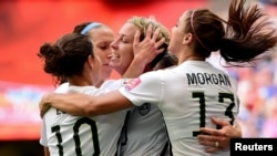 United States forward Abby Wambach (20) is congratulated by midfielder Carli Lloyd (10) and forward Alex Morgan (13)\ after scoring against Nigeria during the first half in a Group D soccer match, June 16, 2015.