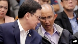 Former chief of the Philippine National Police Criminal Investigation and Detection Group (PNP-CIDG) and now Mayor Benjamin Magalong, right, talks to Justice Secretary Menardo Guevarra at the resumption of the Senate probe on the release of hundreds…