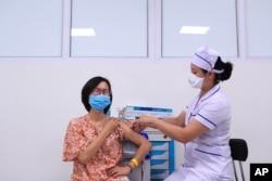 FILE - A woman receives a shot of AstraZeneca COVID-19 vaccine in Hanoi, Vietnam, June 27, 2021.