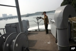 FILE - A North Korean guide poses near a machine gun on the spy ship USS Pueblo, now a tourist attraction in Pyongyang.
