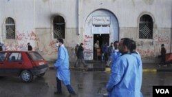 Médicos voluntarios libios pasan frente a la corte de Benghazi, tratando de atender a las personas heridas.