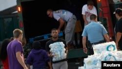 Các tình nguyện viên dỡ các thùng nước uống từ xe tải bên ngoài trường trung học Waite ở Toledo, Ohio, ngày 3/8/2014.