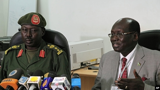 South Sudanese Minister of Information Barnaba Benjamin Marial, right, and Military Spokesman Philip Aguer brief the median Juba, south Sudan about recent fighting between Sudanese and South Sudanese forces along the north-south border, FILE March 27, 201