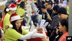 "Shoppers pay for their purchases at an Old Navy store as ""Black Friday"" shoppers get an early start at the Citadel outlet stores on Thanksgiving in Los Angeles, California November 24, 2011"