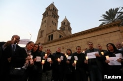 FILE - Egyptians hold candles in front of the Coptic Christian Cathedral in al-Beheira in tribute to the victims of a bomb attack inside a Coptic cathedral in Cairo, Dec. 17, 2016.